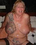 Stark t�towierte MILF-Frau zeigt sich nackt